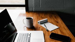 机の上のラップトップとメモ