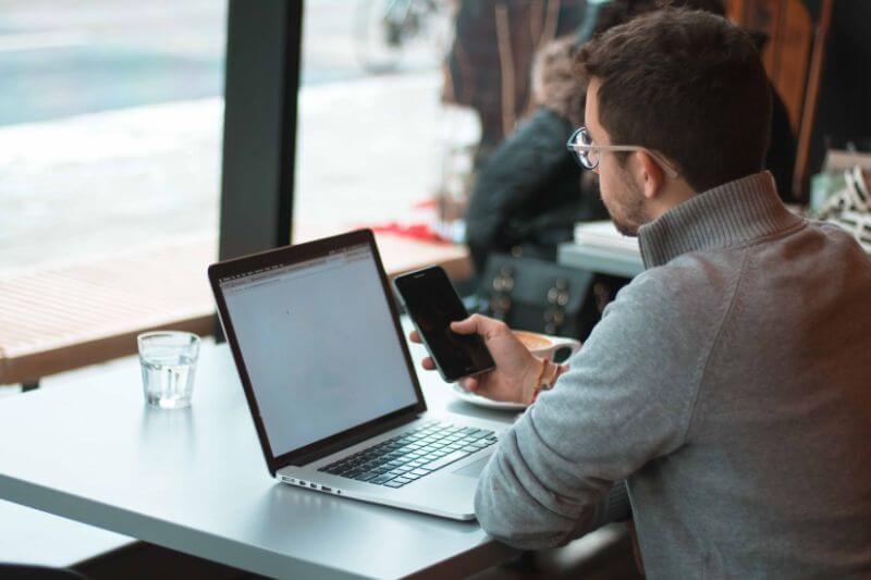 カフェでノートパソコンとスマホを触る男性